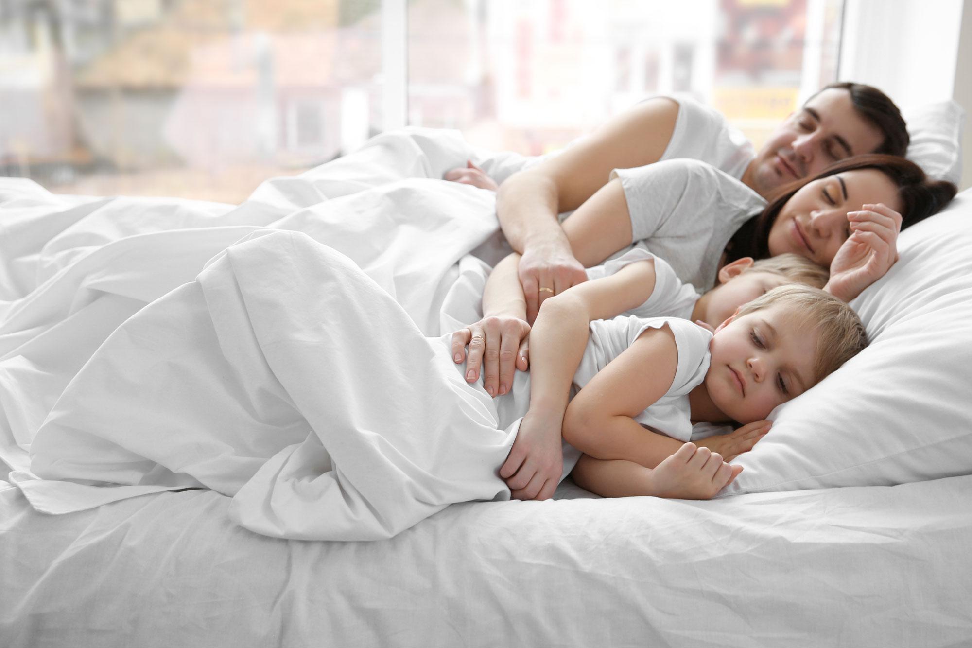 Familie entspannt im Bett